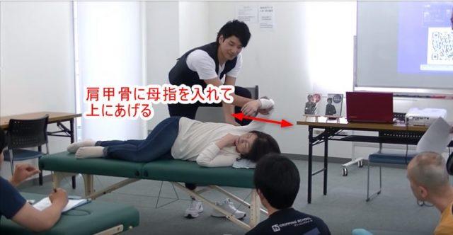 肩甲骨の内側に母指を入れて上にあげる